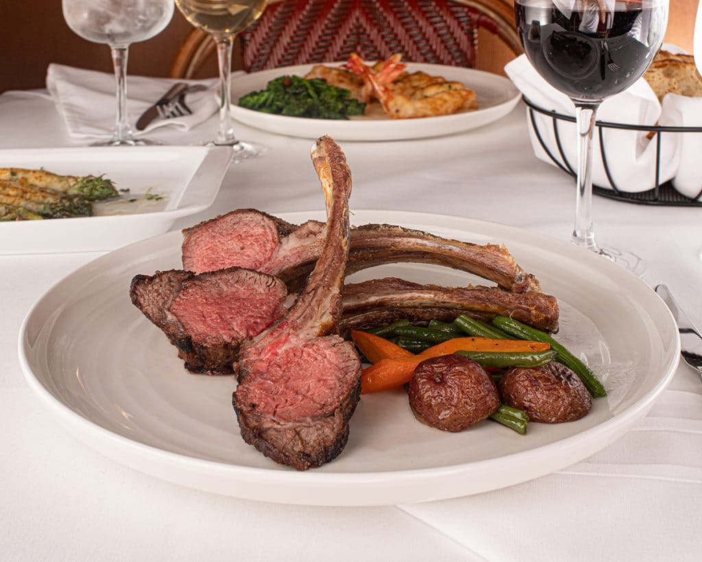 Colorado Rack of Lamb dish with vegetables and baked potato next to it